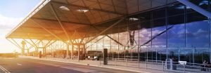terminal stansted panorama 300x104 - STANSTED AIRPORT, LONDON UK - 23 FEBRUARY 2014: airport building with sun light and sky reflection